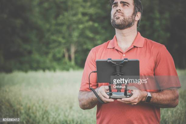 Man Pilot Using Drone Remote Controller at Sunset