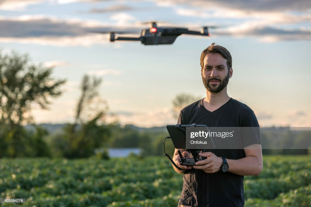 Man Pilot Using Drone Remote Controller at Sunset : Stock Photo