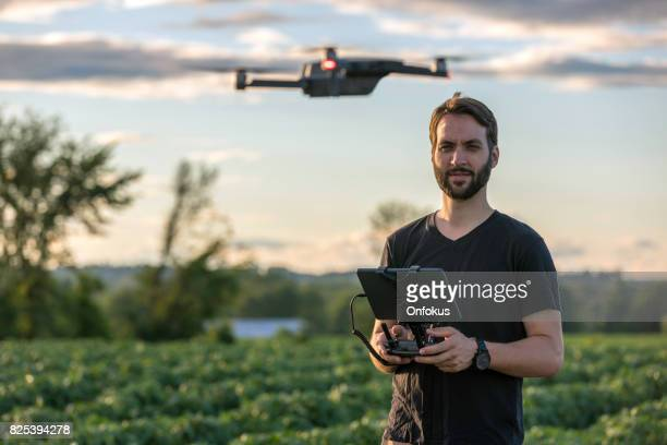 man pilot using drone remote controller at sunset - drone stock pictures, royalty-free photos & images