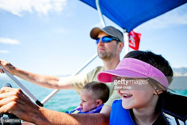 A man pilots a pontoon boat while his three year old son helps steer, and his five year old daughter sits next to them, Bear Lake, Utah.