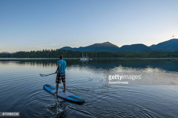 Man pilots stand up paddle board, ocean lagoon