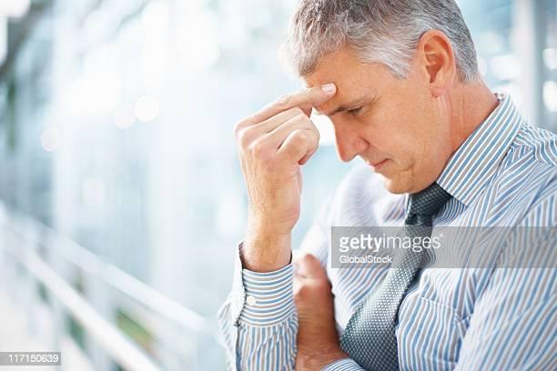 A man pinching his forehead indicating a headache