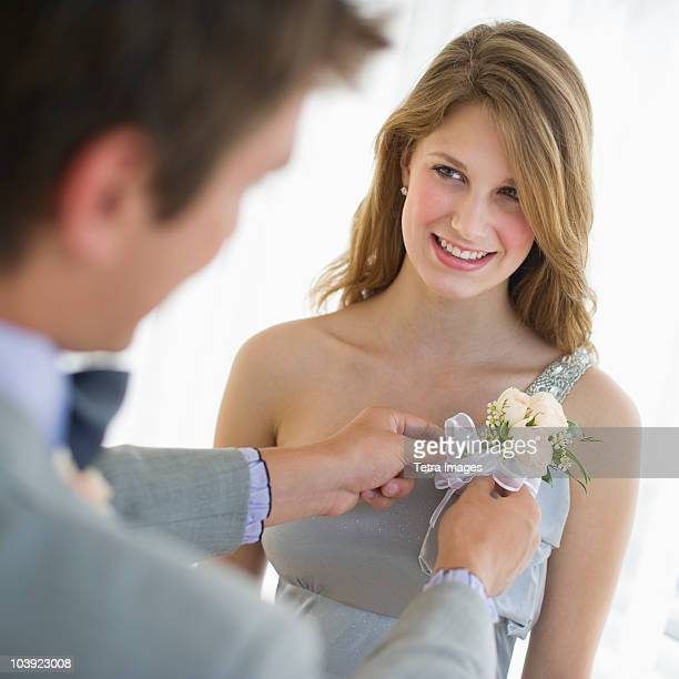 Man pinning corsage on his date's prom dress