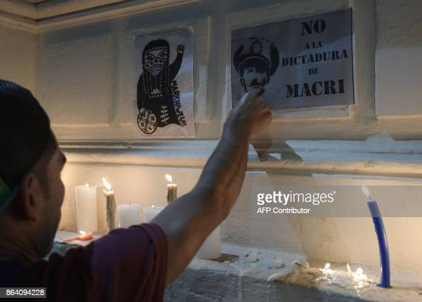 A man places a banner against Argentine President Mauricio Macri outside the judicial morgue where the corpse of Santiago Maldonado disappeared on...