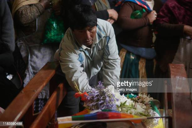 A man places a bouquet of flowers over the body of a man killed yesterday during clashes between supporters of Evo Morales and security forces in the...