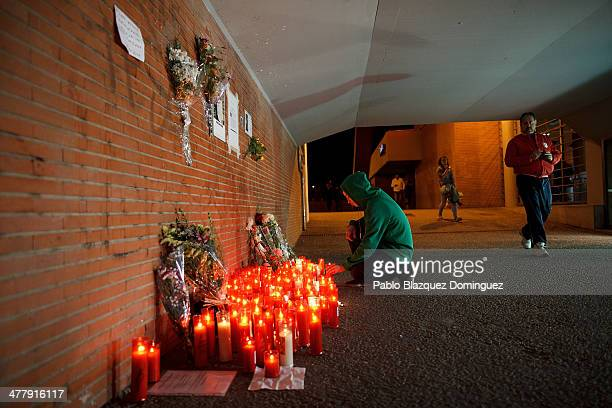 A man places a candle for the victims of Madrid train bombings at El Pozo train station during the 10th anniversary on March 11 2014 in Madrid Spain...