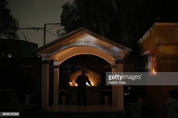 A man places a candle in a tomb at the Jiloptepec pantheon as part of the 'Day of the Dead Celebration' on November 1 2017 in Mexico City Mexico The...