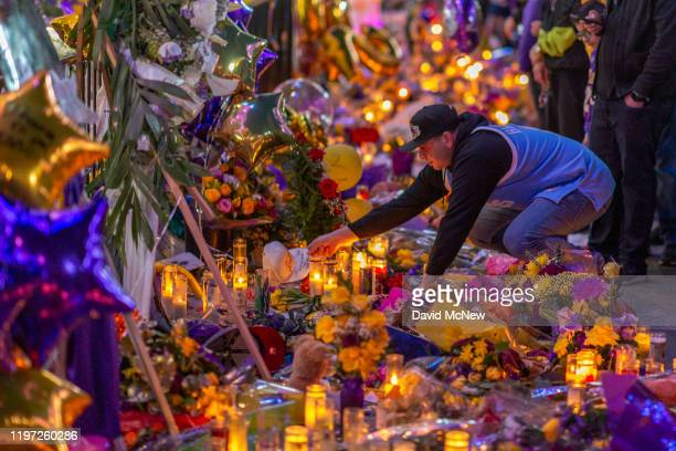 A man places a hat at a makeshift memorial near Staples Center in remembrance of former NBA great Kobe Bryant who along with his 13yearold daughter...