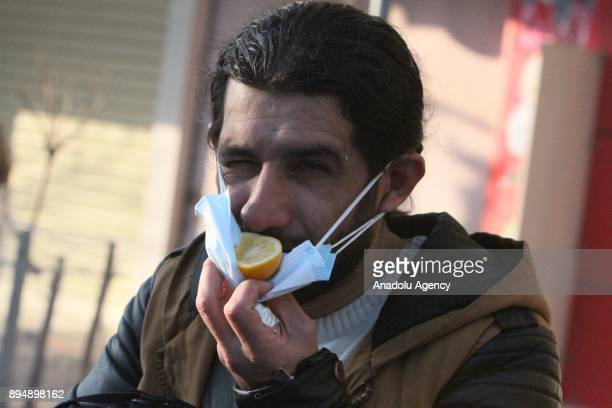 A man places a lemon on his face mask to cover from the tear gas smoke while demonstrators clash with riot police within antigovernment protests in...