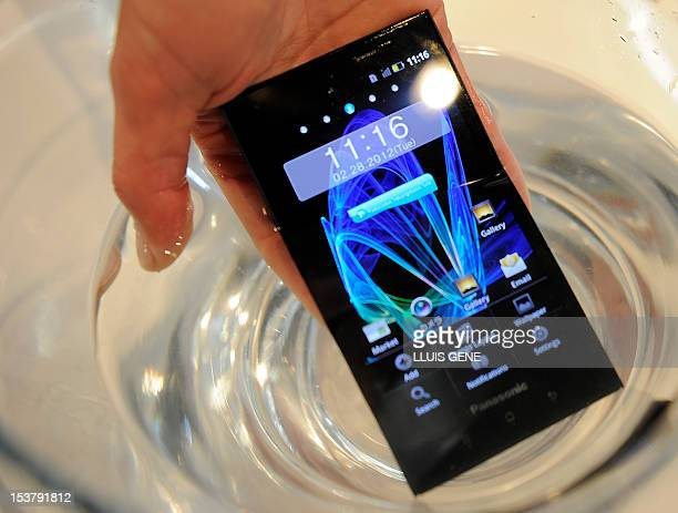 Man places a Panasonic Eluga Power waterproof smartphone on a glass of water during a presentation at the Mobile World Congress on February 28, 2012...