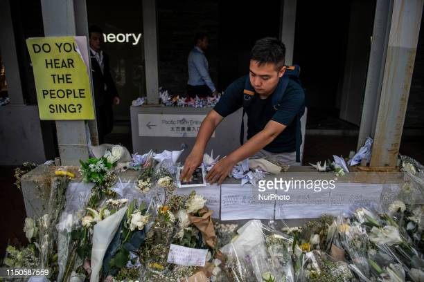 A Man places a peace of paper on a Memorial set up in Honor of a man who died after falling from a scaffolding in Pacific Place while protesting...
