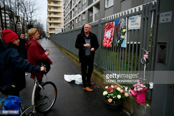 A man places a picture of Mireille Knoll and a message announcing a 'Marche Blanche' condemning the alleged antisemitic motive for of her killing...