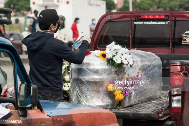 A man places a picture on the coffin of a loved one which is wrapped in plastic with flowers as it is being transported on a truck to the cemetery on...