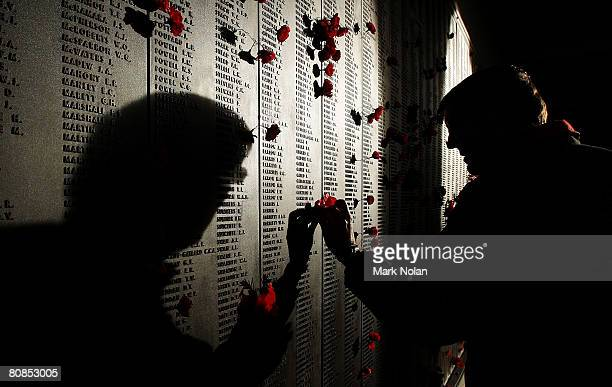 A man places a poppy on the Roll of Honour for World War I after the ANZAC Day Dawn Service at the Australian War Memorial on April 25 2008 in...