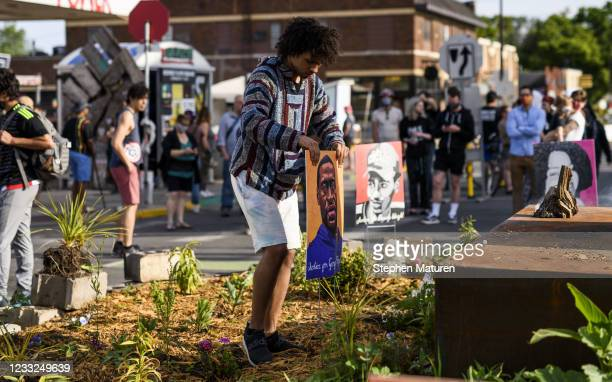 Man places a portrait of George Floyd at George Floyd Square on June 3, 2021 in Minneapolis, Minnesota. Early this morning crews worked to remove...