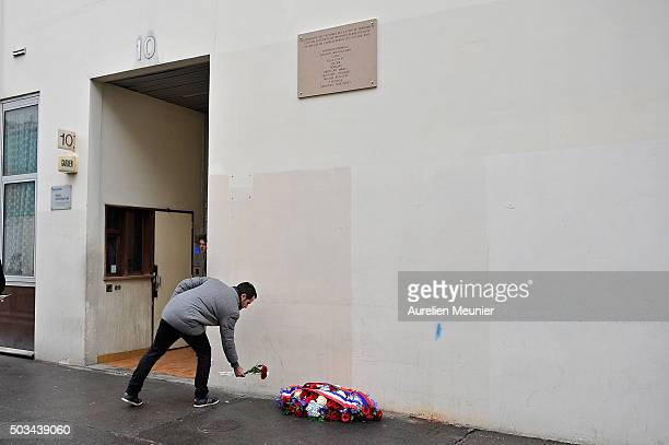 A man places a red rose in front of the former Charlie Hebdo office after the inauguration of the memorial stone on January 5 2016 in Paris France...