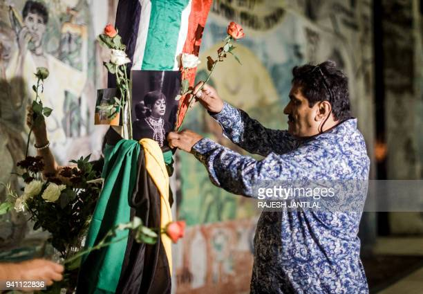 A man places a rose close to the Old Durban Prison's Human Rights wall as he pays his respect to the late South African highprofile antiapartheid...