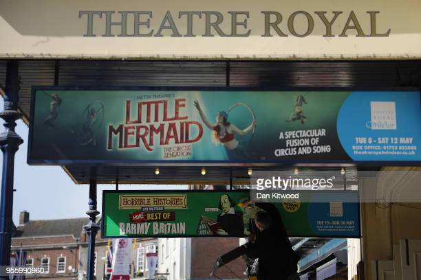 A man places advertising boards outside the Theatre Royal as the town prepares for the wedding of Prince Harry and his fiance US actress Meghan...