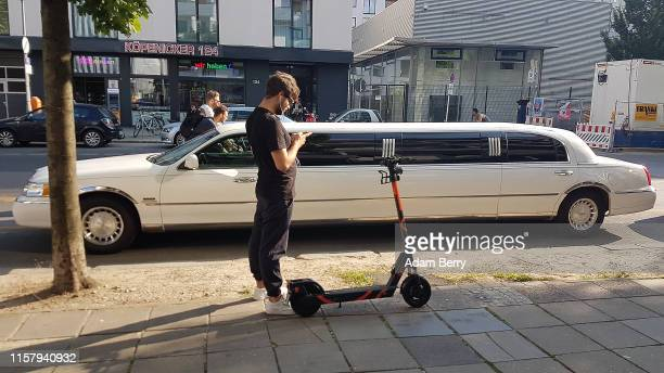 A man places an order for a Circ electric scooter in front of a limousine on June 22 2019 in Berlin Germany After the scooters became legal this...