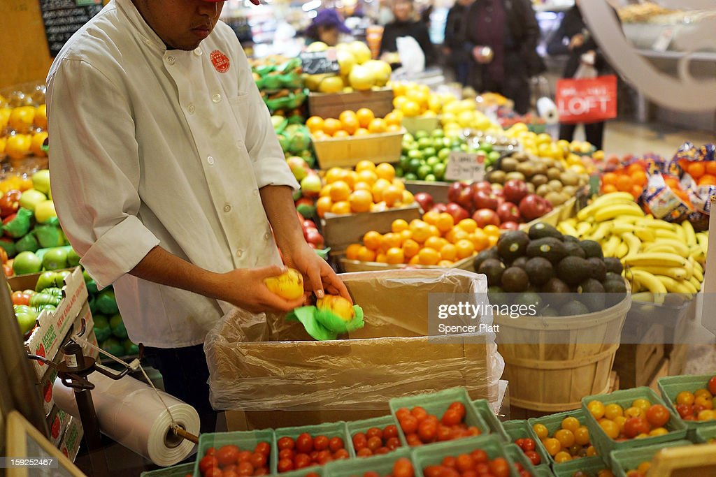 A man places bruised fruit in a bin at a market on January 10, 2013 in New York City. A new London-based study by the The Institution of Mechanical Engineers found that as much as half of the food produced in the world ends up going to waste. The study found that irresponsible retailer and consumer behavior contributed to 1.2 billion to two billion of the four billion metric tons of food produced globally that goes uneaten.