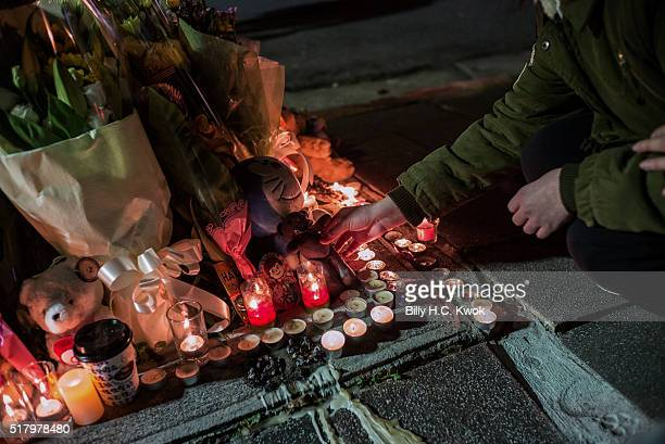 A man places candles at a makeshift memorial where a girl was found decapitated by a knifewielding assailant outside a subway station on March 28...