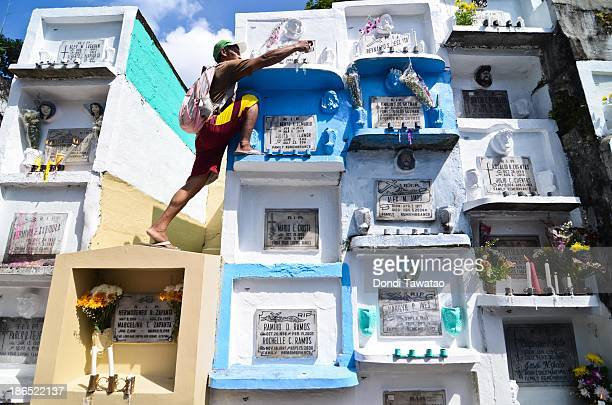 CITY PHILIPPINES A man places candles on the crypt of a loved one at a public cemetery as All Saint's Day is celebrated on November 1 2013 in...