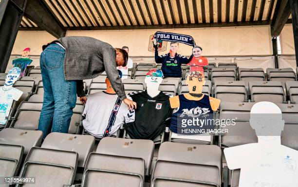 A man places cardboard figures with pictures of the fans in the empty tribunes of the Ceres Park Football Stadium on the eve of the Danish Superliga...