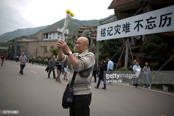 A man places flowers ans mourns for the victims of the earthquake at a park at the Beichuan town in Sichuan province on April 24 2013 in Chengdu...