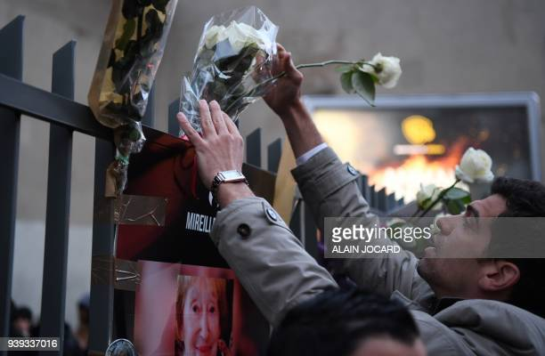 A man places flowers as he gathers with others at the entrance to an apartment building in Paris on March 28 at the conclusion of a march in memory...