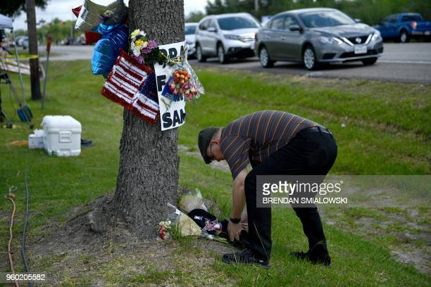 A man places flowers at a makeshift memorial at Santa Fe High School on May 19 in Santa Fe Texas Ten people mostly students were killed when a...