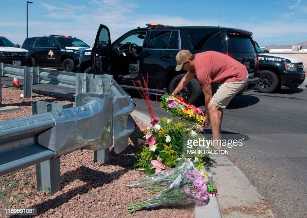 A man places flowers at a makeshift memorial outside the Cielo Vista Mall WalMart where a shooting left 20 people dead in El Paso Texas on August 4...