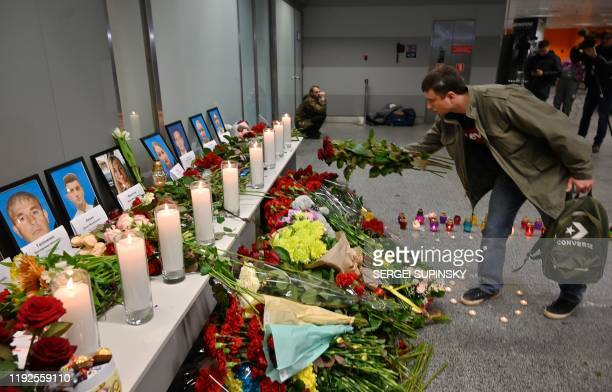 A man places flowers at a memorial for the victims of the Ukraine International Airlines Boeing 737800 crash in the Iranian capital Tehran at the...