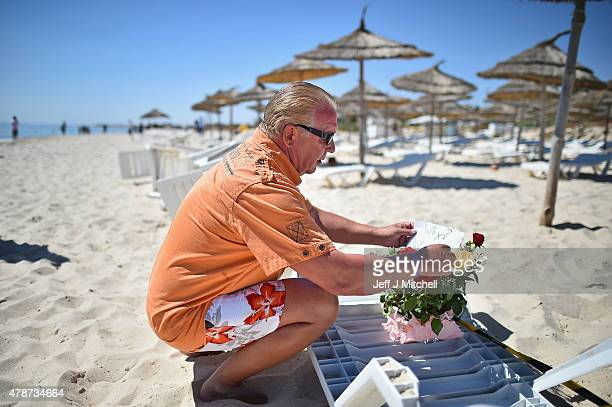 A man places flowers at the beach next to the Imperial Marhaba Hotel where 38 people were killed yesterday in a terrorist attack on June 27 2015 in...