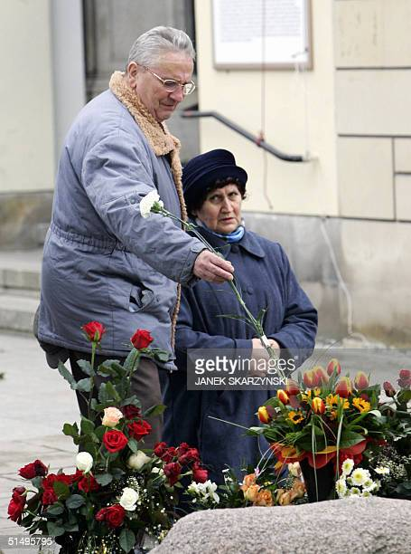 A man places flowers at the grave of Polish priest Jerzy Popieluszko 19 October 2004 in Warsaw to commemorate the 20th anniversary of Popieluszko's...