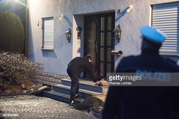 A man places flowers in front of the residence of the parents of Andreas Lubitz copilot on Germanwings flight 4U9525 on March 26 2015 in Montabaur...