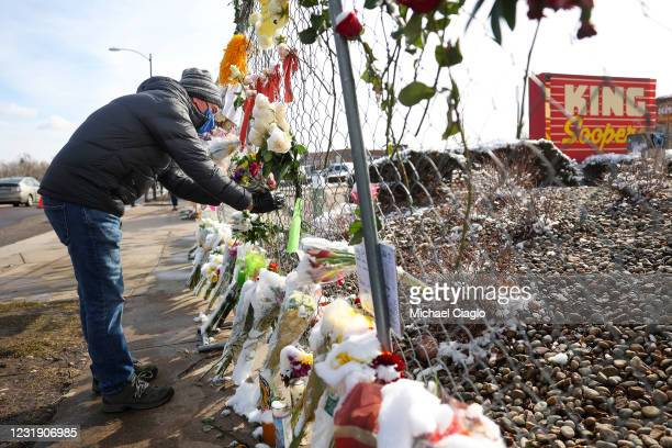 Man places flowers in the fence at a makeshift memorial for the victims of a mass shooting outside a King Soopers grocery store on March 24, 2021 in...