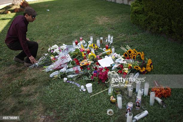 A man places flowers on the lawn of the Alpha Phi sorority house May 25 2014 in Isla Vista California According to reports 22 year old Elliot Rodger...