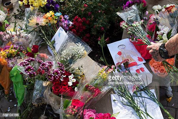 A man places flowers outside the Muhammad Ali center where mourners created a makeshift memorial for the boxer June 4 2016 in Louisville Kentucky Ali...