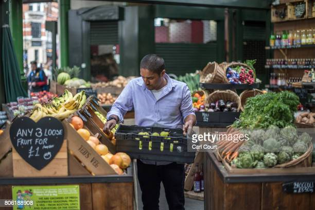 A man places fruit and vegetables on display at a stall in Borough Market on July 3 2017 in London England On 3 June 2017 Islamist terrorists...