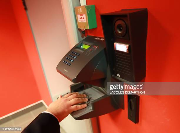 A man places his hand during an identity check by manual fingerprint recognition to open the security lock at the Equinix Paris data centre called...