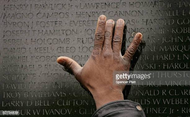 A man places his hand on the Vietnam Veterans Memorial where the names of 58 thousand Americans killed in the Vietnam War are listed April 29 2005 in...