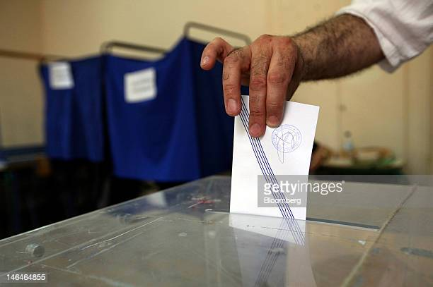A man places his sealed and stamped ballot paper into a box as he casts his vote in the second round of the Greek general elections at a polling...