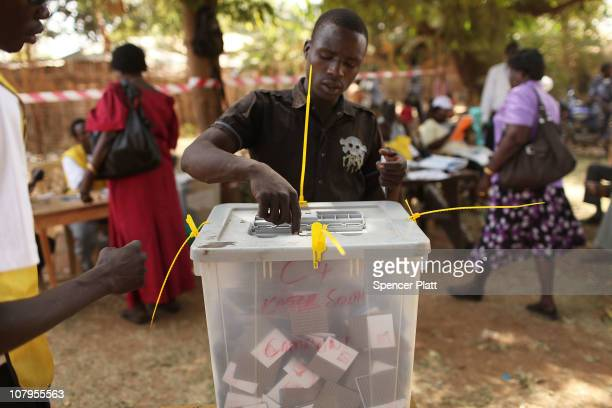 A man places his vote in a plastic box at a polling station during the second day of voting for the independence referendum January 10 2011 in Juba...