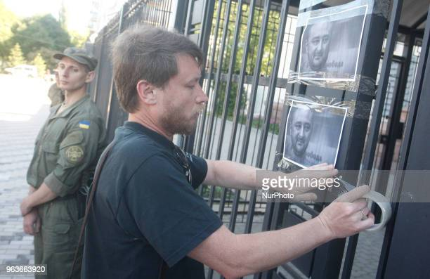 A man places the portraits of killed Russian journalist Arkady Babchenko on a fence of Russian embassy in Kyiv Ukraine 30 May 2018 Russian journalist...