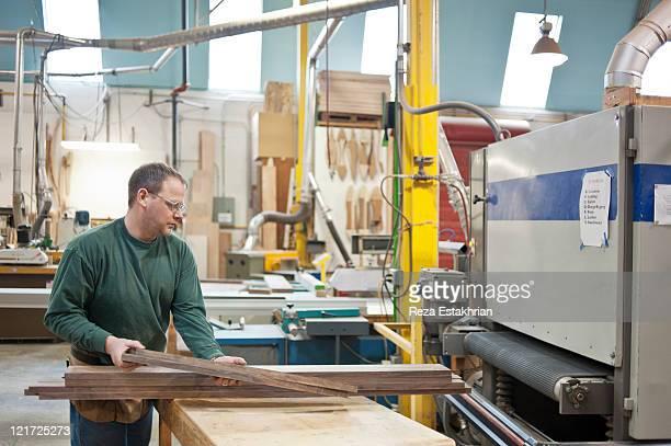 Man places walnut in industrial sander