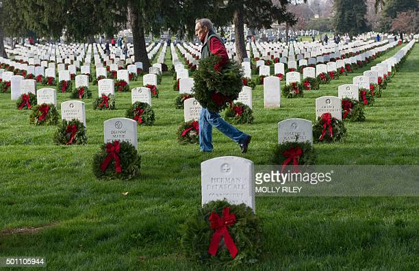 A man places wreaths at gravesites during the 2015 National Wreaths Across America event at Arlington National Cemetery on December 12 2015 in...