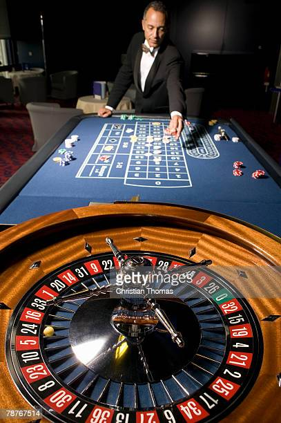 man placing a bet at the roulette table - gambling table stock pictures, royalty-free photos & images