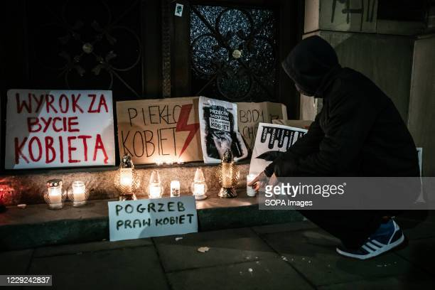 A man placing a candle at the entrance to the Krakow office of the ruling Law and Justice party during the protest The Polish Constitutional Court...