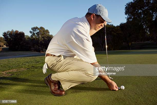 Man Placing a Marker Behind His Golf Ball