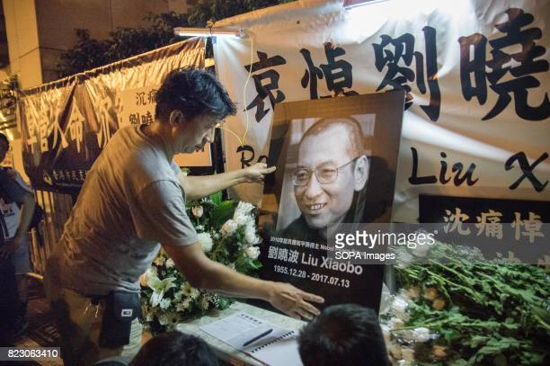 A man placing a picture of Liu Xiaobo at the temporary memorial area Residents of Hong Kong hosted a vigil service outside the Chinese Liaison Office...